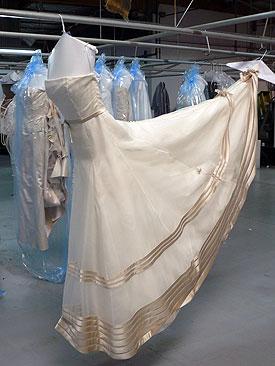 accrocher une robe de mariée dans l'atelier