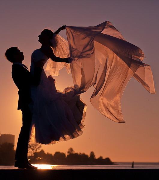 l'homme embrasse son épouse dans robe mariage au coucher du soleil