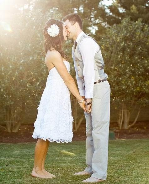 un couple s'embrasse à pieds nus sur la pelouse