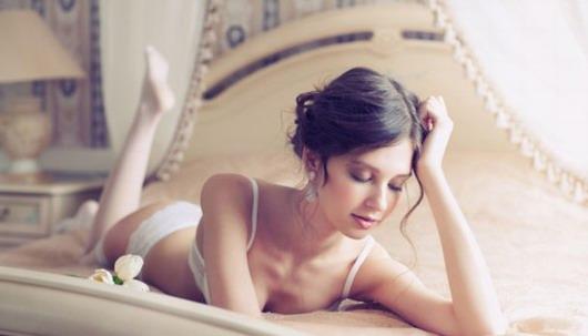 femme sexy portant un ensemble de lingerie sur le lit