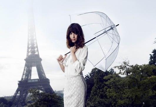 Alexa Chung s'habille en blanc portant une parapluie transparent devant la Tour Eiffel