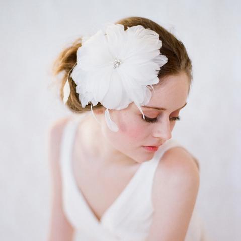 Une Coiffure de mariage ornée des plumes en forme de fleur se marie une robe de mariée simple à col-V