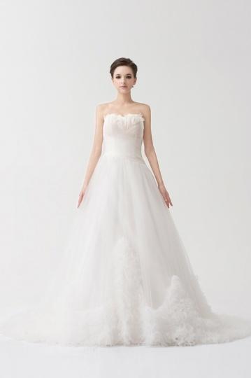 Robe blanche de mariée ruchée ornée de plumes